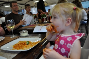 Family from Portland (background) observe Charlotte with Pasta Bolognese