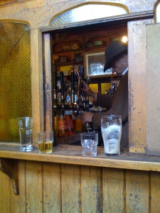 "Bartender, seen through the window of the ""snug"""